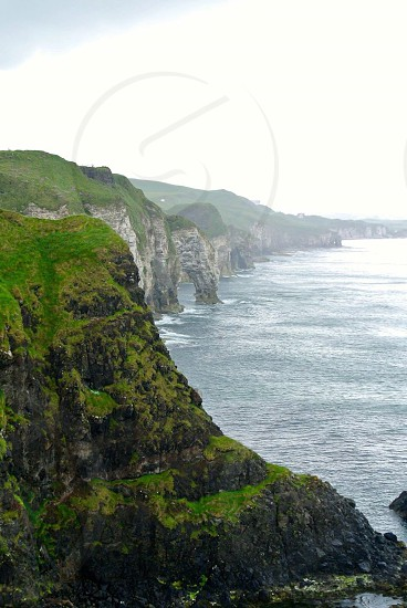 cliff near body of water at cloudy sky at daytime photo