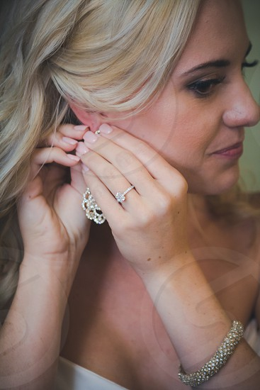 blonde woman putting earring on her right ear photo
