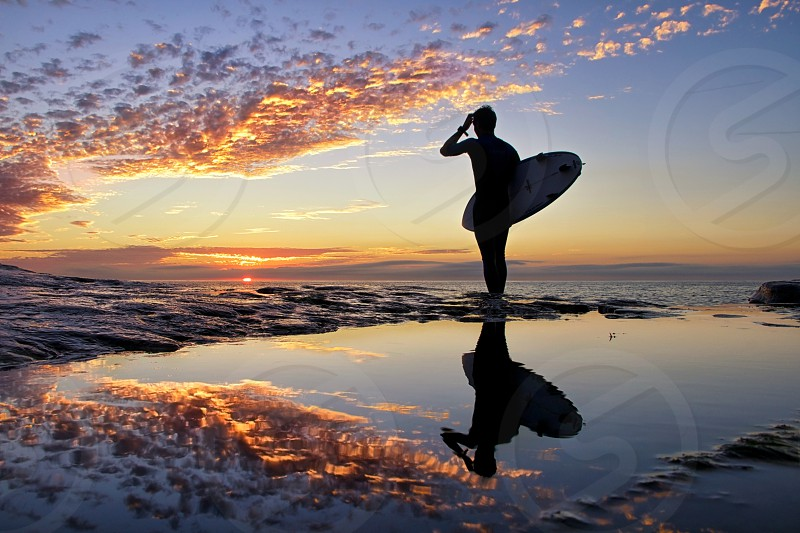 man holding surfboard standing on sand photo