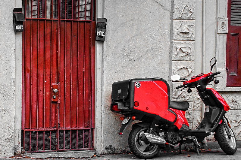 red ad black scooter beside building wall with red gate photo