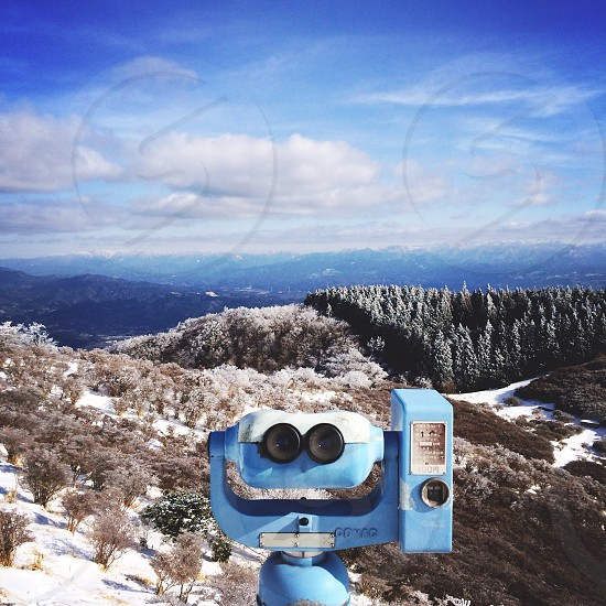 blue telescope and snow covered trees and mountain photo