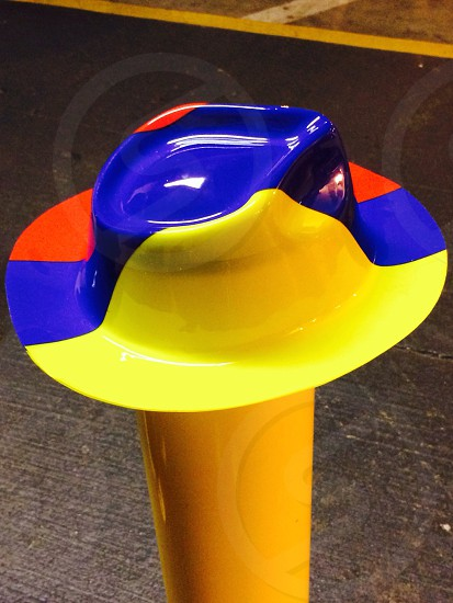 Hat; hat on a post; plastic hat; parking lot; red; yellow; blue photo