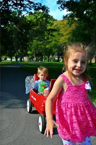 park fun brother and sister blonde children red wagon green trees summer time photo