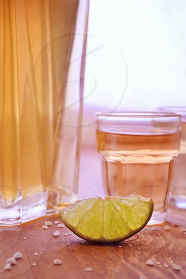 Glass bottle and shot glasses lime and salt photo