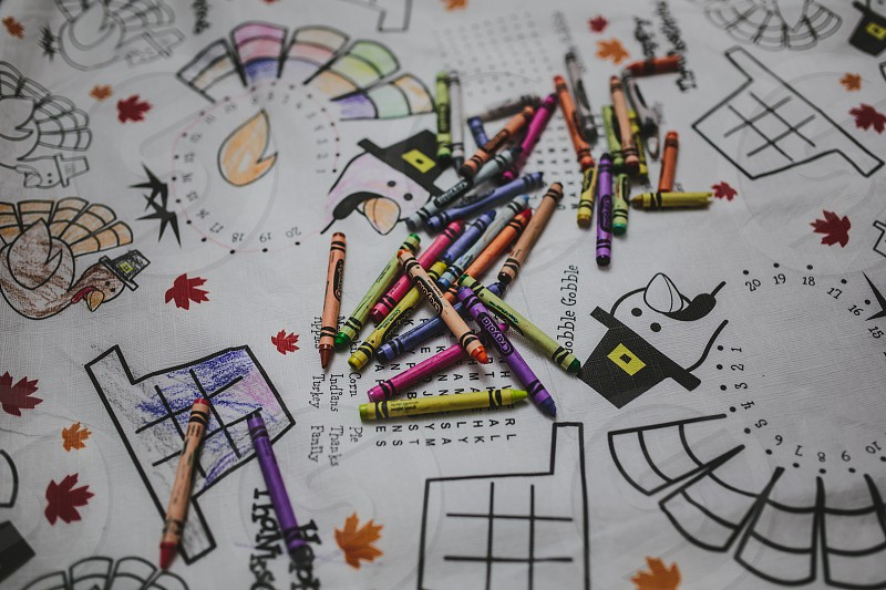 Crayons scattered on a thanksgiving tablecloth. photo