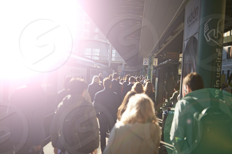 A crowd of commuters walking along a platform on their way to the office in Milan city centre in early morning sunshine photo