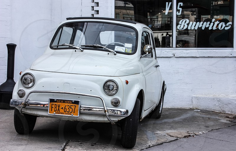 classic white fiat parked in front of a white building with window painted with burritos photo
