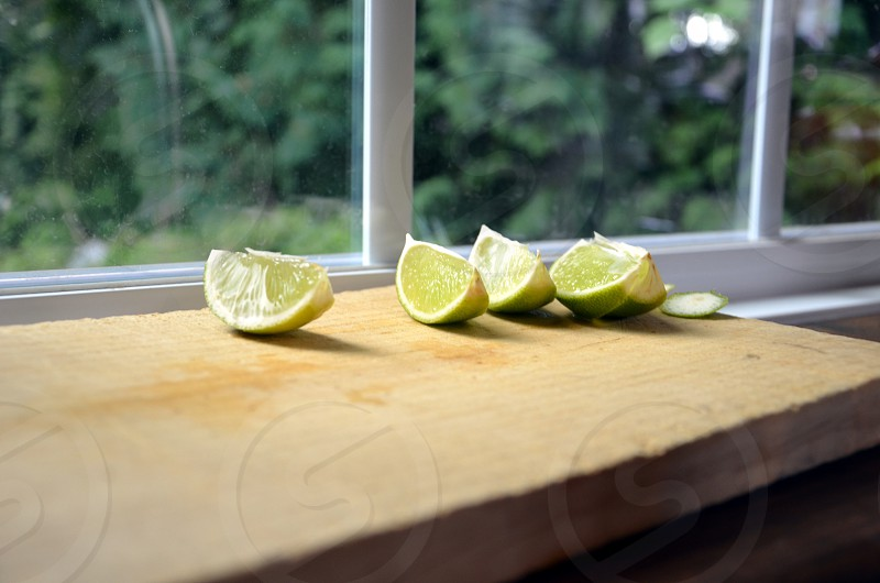Lime slices on wood chopping board photo