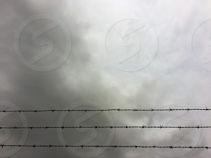 Clouds overcast storm fence barbed wire keep out no trespassing stay away danger lines symmetry simple photo
