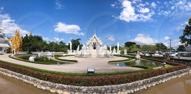 Outdoor day horizontal landscape panoramic colour Wat Rong Khun The White Temple Chiang Rai Thailand Thai Kingdom of Thailand travel tourism tourist wanderlust summer summertime temple Buddhist Buddhism spiritual pure holy dragon monster carved ornate elaborate art modern photo