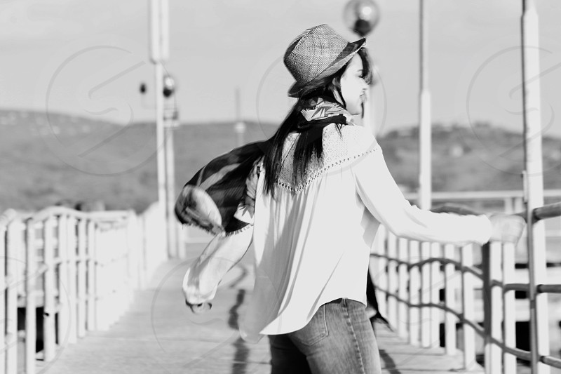 Black and White shot with lady long dark hair and country hat dancing on a lake Platform photo