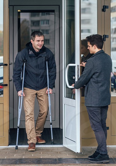 man in grey suit open the door while man in grey jacket walking out from the building using crutches photo