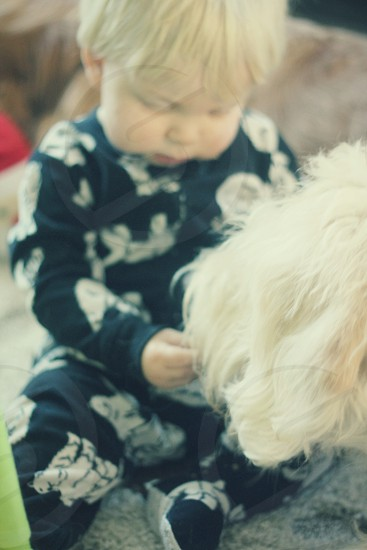 Baby sharing cookie with his dog photo