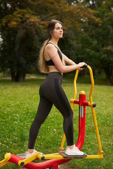 Sporty girl do exercise on the simulator with park background photo