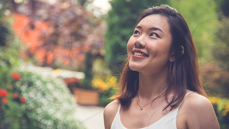 woman wearing white spaghetti strap top looking up while smiling photo photo