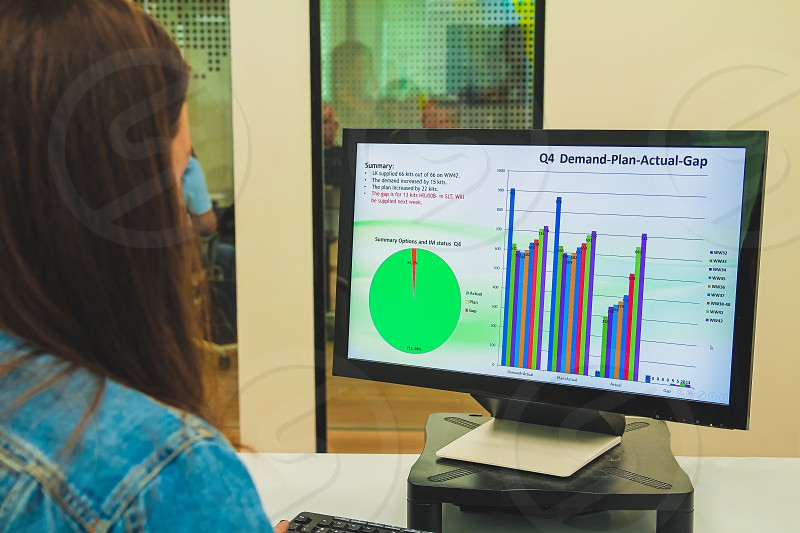 Close up back view of a young businesswoman looking at a screen while working on a desktop computer at her desk at the office. Modern and comfortable interior office. She is analyzing statistic data with graphics charts and diagrams. photo