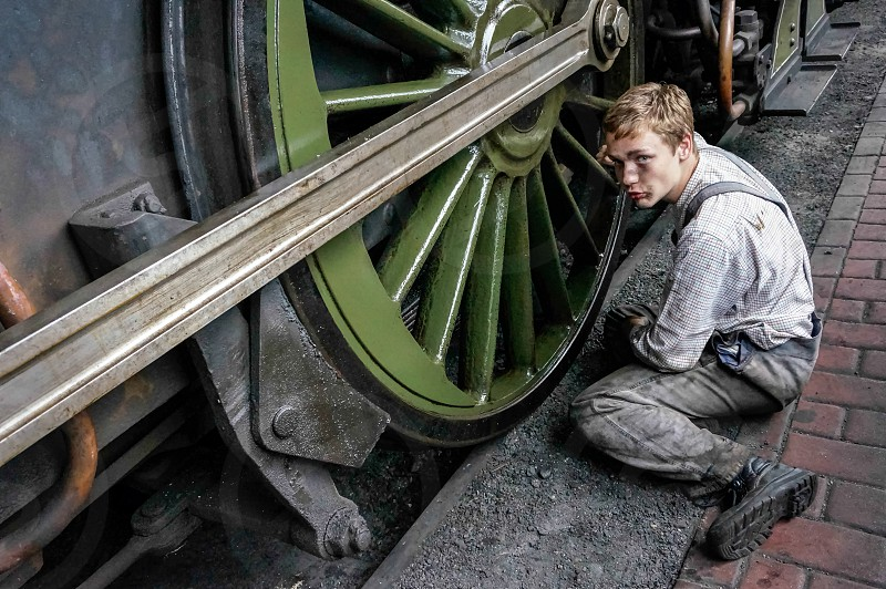 Young Man Cleaning a Steam Train Wheel photo
