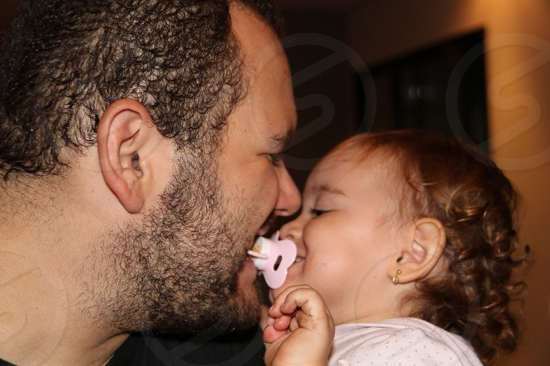 man kissing baby girl with pacifier in mouth photo