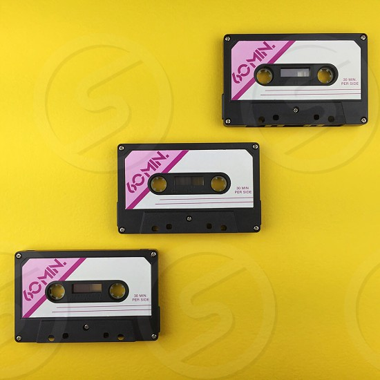 white black and pink 60 min. printed cassette on yellow surface photo