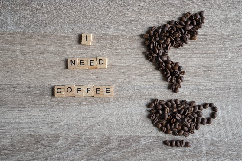 I need coffee word qoute with Roasted coffee beans placed in the shape of a cup and smoke icon on wooden background photo