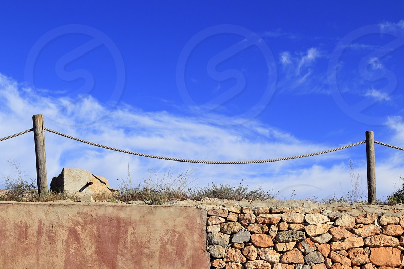 traditional rope fence over stone wall grunge cement blue sky photo