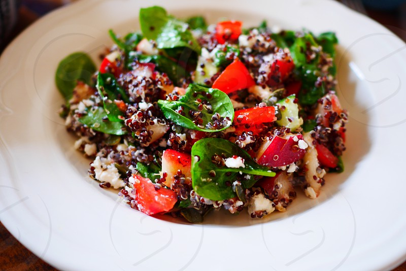 Quinoa salad fresh vegetables seeds tomatoes spinach fruit cheese photo