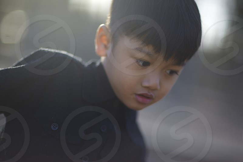 Portrait of a young Asian boy in bright spring sunshine photo