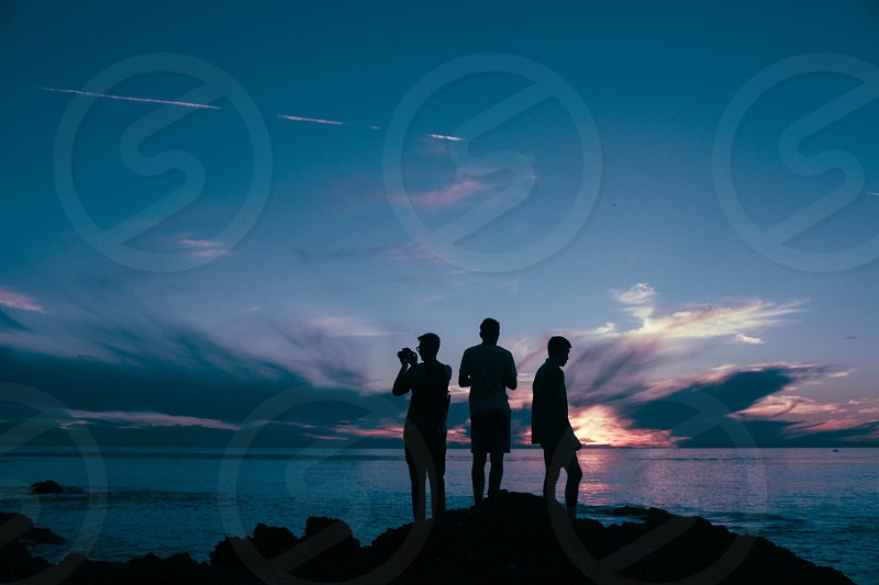 three person standing on rock photo