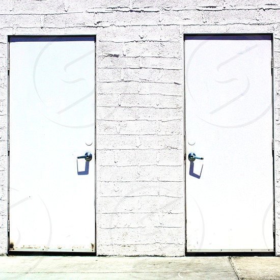 Double white doors on a white building photo