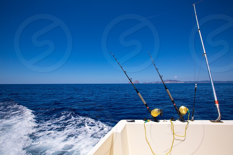 Ibiza fishing boat trolling with rods and reels in blue Mediterranean sea Balearic photo