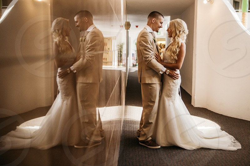 newly wed couple standing on grey carpeted hallway photo