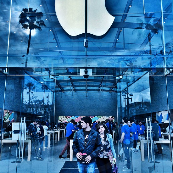 man and woman standing in front of clear glass doors of Apple store photo