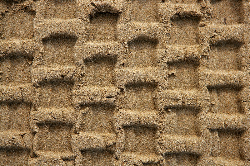 Beach sand texture with vehicle tires footprint background pattern photo
