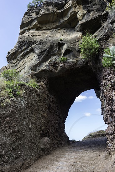 rock on the eastcoast of madeira near Calheta with hole and view to the blue sky photo