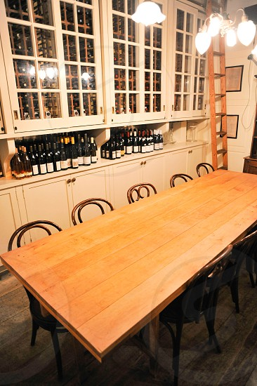 wood dining table with chairs in a room with white wood and glass kitchen cabinets and wine bottle collection with sliding ladder photo