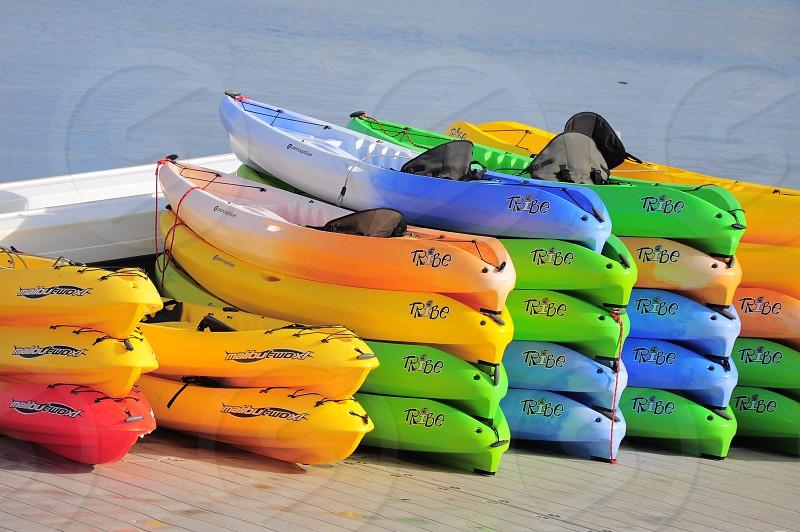 stacks of green blue yellow kayaks photo