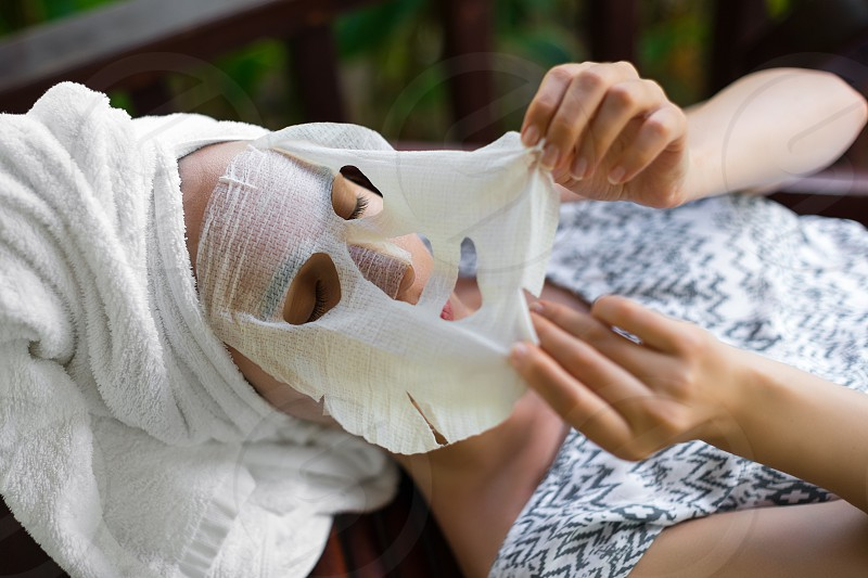 A woman removes a disposable cosmetic mask from her face photo