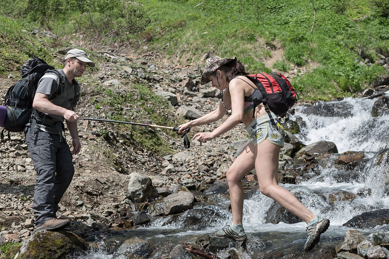 KAMCHATKA PENINSULA RUSSIA - JUNE 23 2012: Summer hiking - tourist man helps a girl-tourist to crossing the mountain river in a summer sunny day on Kamchatka Peninsula. Eurasia Russian Far East Kamchatka Region. photo