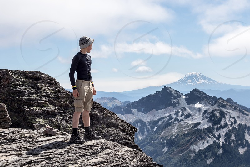 man in black long sleeve and brown cargo shorts standing on mountain cliff facing in mountains under cloudy sky during daytinme photo