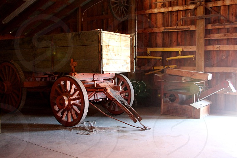 Farm wagon inside a wooden shed lit by the sun photo