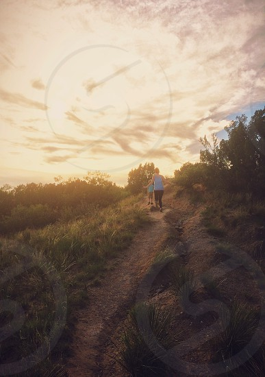 A woman and a little boy run up a trail at sunset.  photo