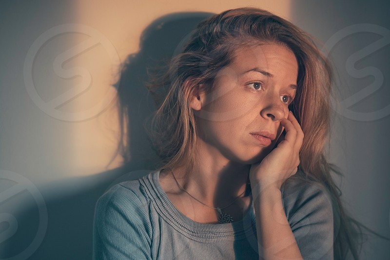 A woman sitting alone and depressed photo