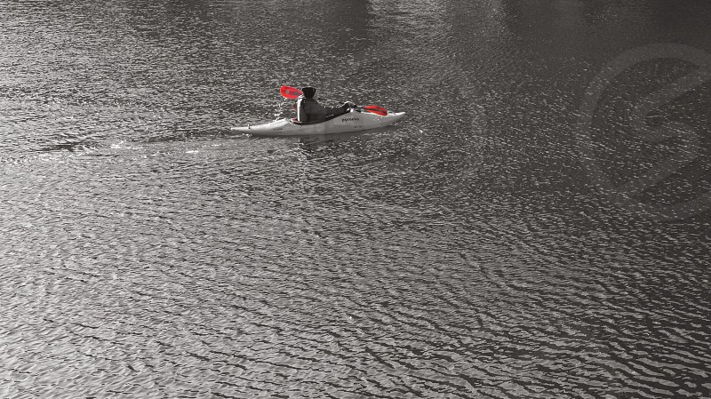 selective color photo of man using kayak with orange paddle photo
