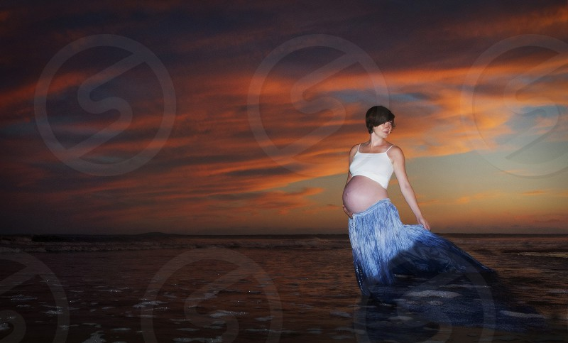 Pregnant woman at beach in ocean at sunset. photo