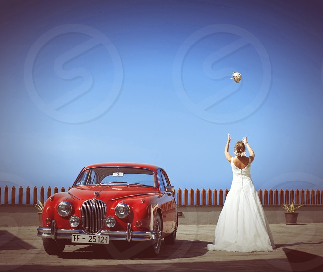 woman standing near red classic car photo