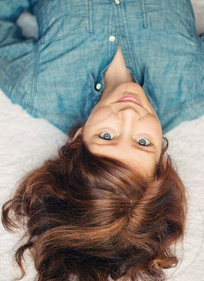 photo of woman wearing blue collard button up shirt smiling while lying on white textile photo