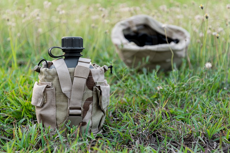 Army water canteen wiht  desert cover on green grass and blurred military helmet background royalty outdoor photo green white river travel canteen day pouch drink soldier thirsty helmet military grass stock tube gear equipment bottle combat cover boiling free flask empty company picture sky desert refreshment army strap hunting background container water thirst photograph image man camping dry memorial hydration moulle photo