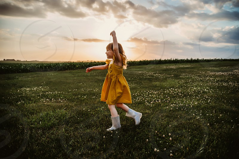 Little girl dancing at sunset in a yard full of clover. photo