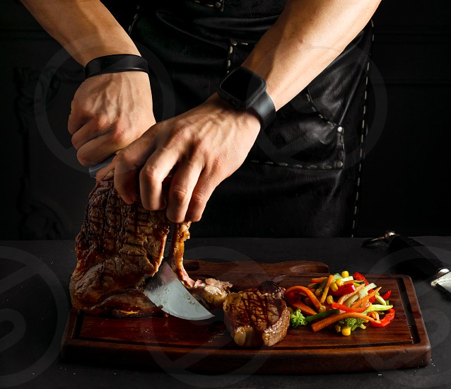 Restaurant chef cutting grilled meat getting ready to serve the dish photo