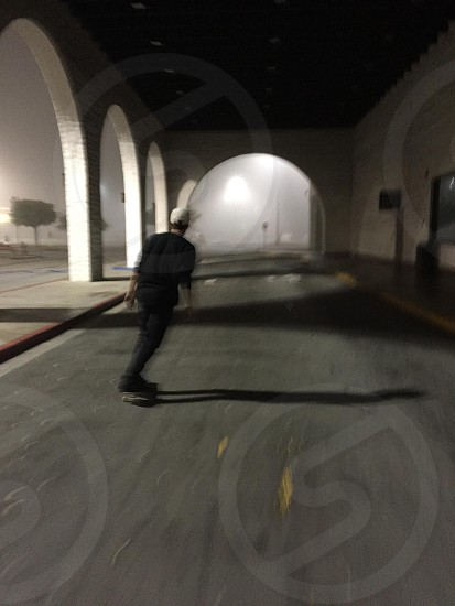 person wearing black shirt riding skateboard in tunnel at night photo
